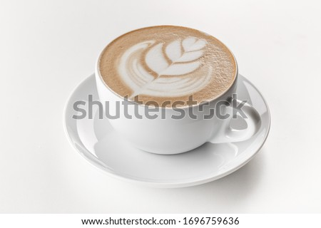 Cappuccino coffee with latte art on top in white ceramic mug. White background.