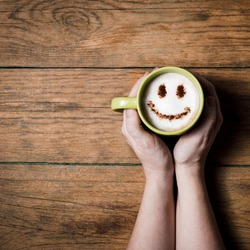Cappuccino coffee with smiley face on wooden table in female hands overhead view