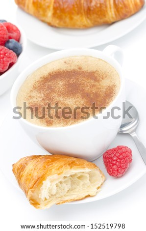 cappuccino, croissant and fresh raspberry for breakfast, on white