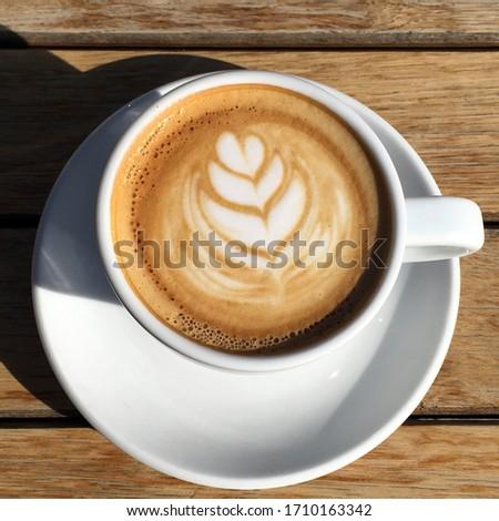 cappuccino cu un model de rosetta latte art în spuma de lapte crema pe o masă de lemn Imagine de stoc ©
