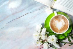 cappuccino cup and book on marble top table