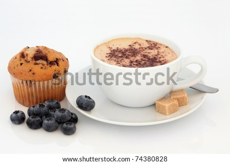 Cappuccino cup and saucer with chocolate chip muffin and loose blueberry fruit, over white background.