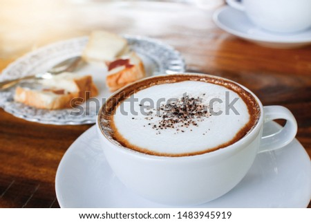 Cappuccino.Cup of Cappuccino Coffee on wooden table With bread beside,Top view #1483945919