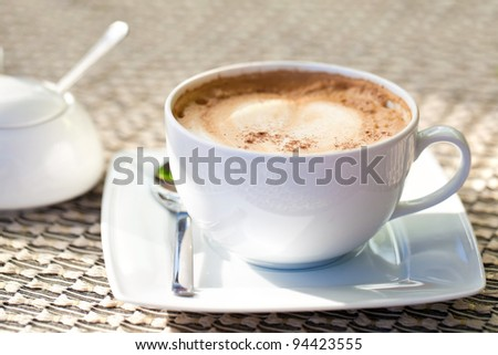 Cappuccino cup on a table with sugar-basin