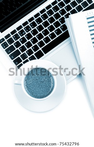Cappuccino cup on laptop. Blue toned, above view, isolated on white