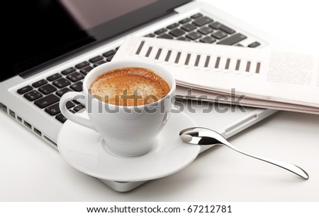 Cappuccino cup on laptop. Small DOF