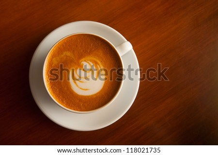 cappuccino cup on the dark brown table