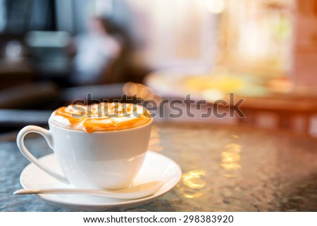 Cappuccino cup on the table, blur coffee shop background