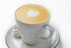 Cappuccino cup with heart shaped foam. Isolated on white background. Coffe in a small white cup. Close up.