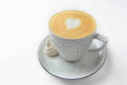 Cappuccino cup with heart shaped foam. Isolated on white background. Coffe in a small white cup. Copy space banner.