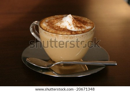 cappuccino glass cup with milk foam and cinnamon