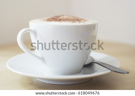 Cappuccino in a porcelain cup on wooden table