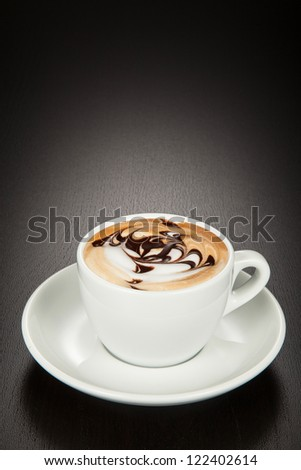 Cappuccino in a white cup and saucer on a black wooden background.
