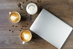 Cappuccino on a table with a laptop on a wooden background with grains of confe