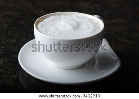 Cappuccino on saucer with black background