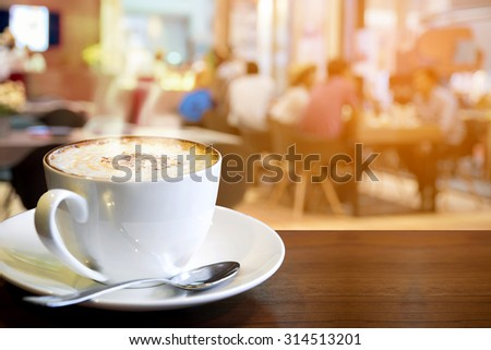 Cappuccino on the table with blur people in coffee shop background