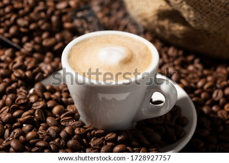 Cappuccino or Coffee with milk cup and roasted beans. Coffee background