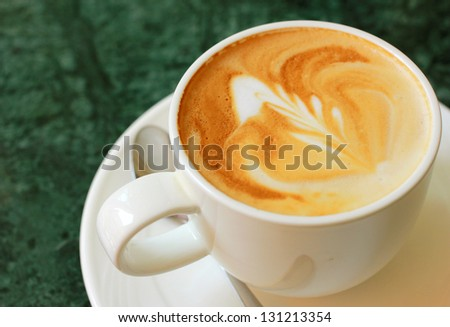Cappuccino or latte coffee with spoon
