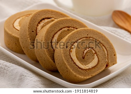 Cappuccino roll cake, swiss roll cake, swiss log cake, jelly roll, roulade cake or sponge roll with cappuccino flavor, served on the rectangle white plate for a coffee break.