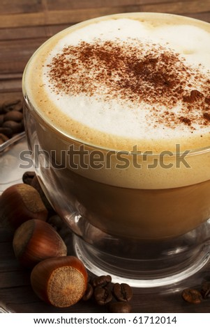 cappuccino with chocolate powder on milk froth and hazelnuts on wooden background