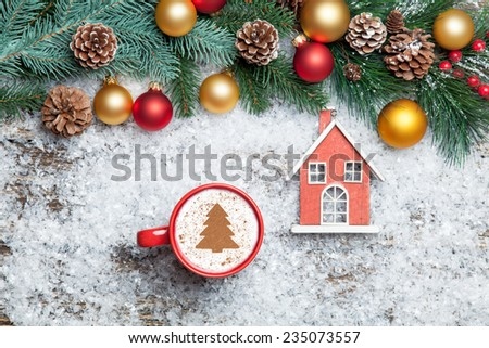 Cappuccino with christmas tree shape and toy home on artificial background.