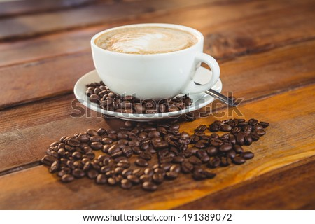 Cappuccino with coffee beans on table in cafeteria