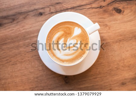 Cappuccino with frothy foam, blue coffee cup top view closeup on white wood background. Flat lay style. Stok fotoğraf ©