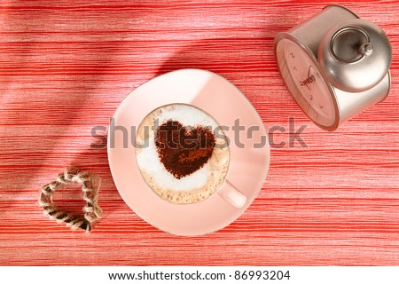 cappuccino with old alarm clock and cocoa heart on red stripy backdrop