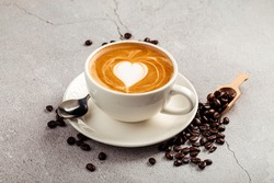 Cappucino coffee with heart shape art in a white cup on the concrete background with beans