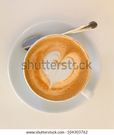 Cappucino with heart shape foam on white saucer with spoon