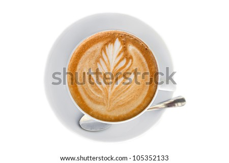 Cappucino with leaf shape foam on white saucer with spoon