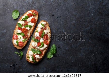 Caprese bruschetta toasts with cherry tomatoes, mozzarella and basil. Top view with space for your text Stock fotó ©