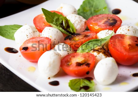 Caprese: cherry tomato, mozzarella balls and basil leaves