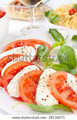 caprese salad and linguine pasta with tomato sauce at the back