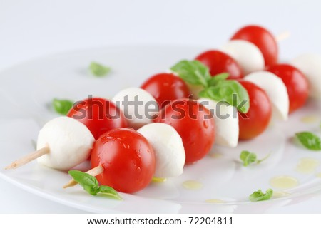 Caprese salad. Cherry tomatoes and mozzarella on skewers, garnished with basil leaves and olive oil