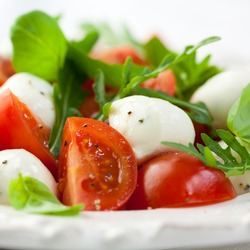 Caprese salad. Healthy meal with cherry tomatoes, mozzarella balls, spices, fresh rocket and basil. Home made, tasty food. Symbolic image. Concept for a tasty and healthy vegetarian meal.  Close up.