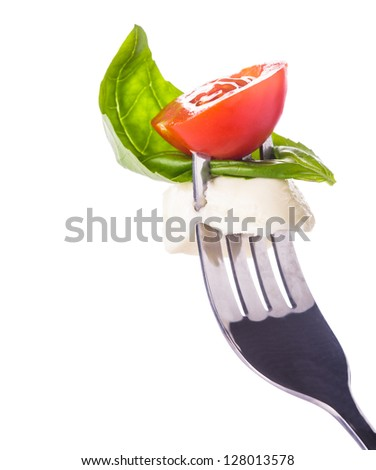 Caprese salad ingredients on the fork isolated on white
