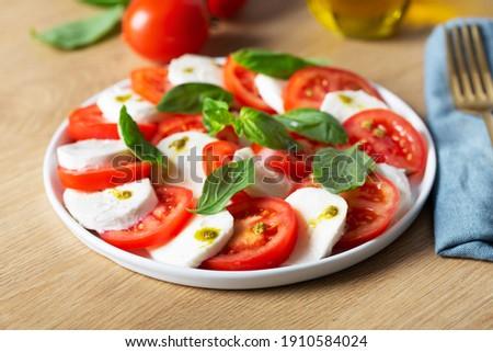 Caprese salad. Italian famous salad with fresh tomatoes, mozzarella cheese and basil, close up shot Stok fotoğraf ©