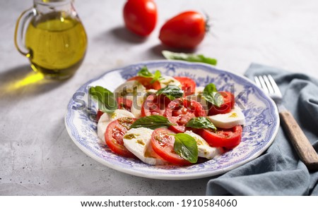 Caprese salad. Italian famous salad with fresh tomatoes, mozzarella cheese and basil on the gray background Stok fotoğraf ©