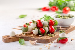 Caprese salad-mozzarella, basil, cherry tomatoes, pesto sauce, skewers. Italian homemade food and a healthy diet concept.