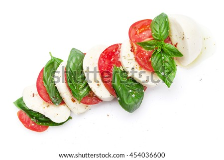 Caprese salad. Mozzarella cheese, tomatoes and basil herb leaves. Isolated on white background. Top view - Shutterstock ID 454036600