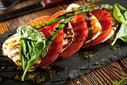 Caprese Salad - Salad with Tomatoes, Mozzarella Cheese, Basil, Asparagus and Balsamic. Salad Dressing with Pesto Sauce
