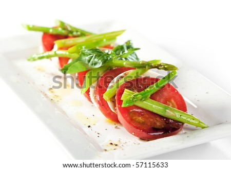 Caprese Salad - Salad with Tomatoes, Mozzarella Cheese, Green Asparagus and Basil Leaf - stock photo
