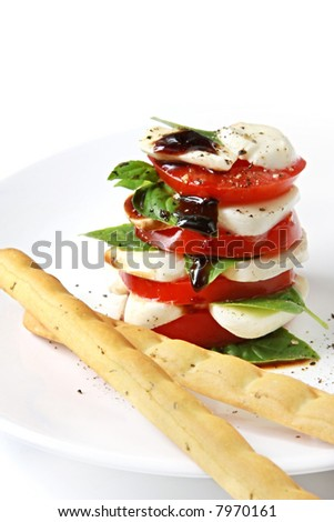 Caprese Salad.  Stack of vine-ripened tomatoes, sweet basil, and baby mozzarella or bocconcini.  With a balsamic reduction, and Italian breadsticks.