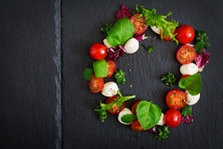 Caprese salad tomato and mozzarella with basil and herbs oon black background. Top view