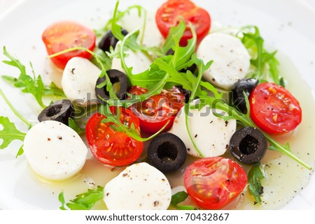 Caprese salad with mozzarella, tomatoes and black olive