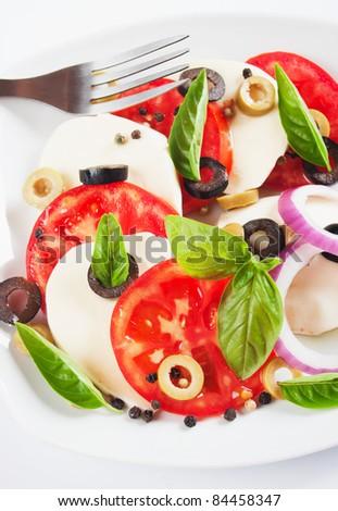 Caprese salad with tomato, basil, olives and mozzarella cheese - stock photo