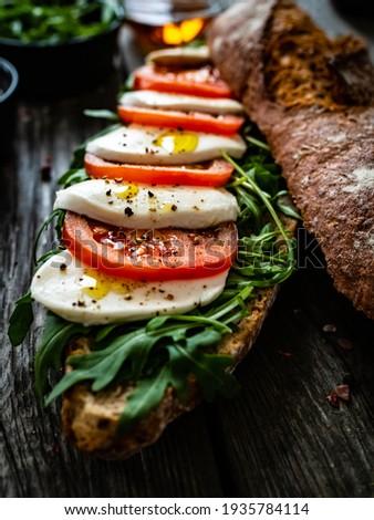 Caprese sandwich with tomato, mozzarella and arugula on wooden table Zdjęcia stock ©