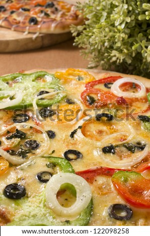 Capsicum Pizza with leaves and Sausage Pizza in Background