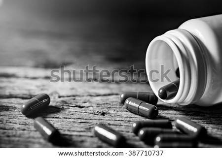 capsule pill with bottle on wooden floor ,back and white tone. #387710737
